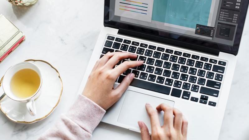 Pessoa usando notebook em mesa de escritório com caderno e xícara de chá.