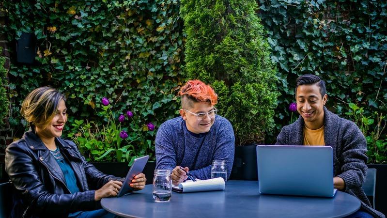 Dois homens e uma mulher sentados na mesa