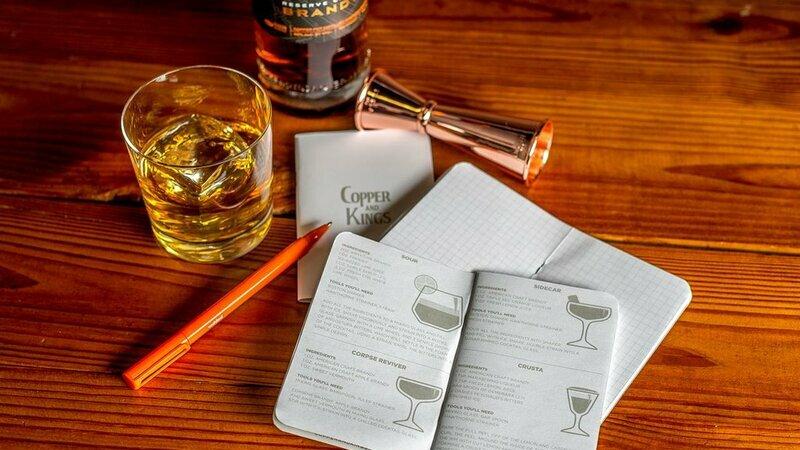 Cadernos sobre mesa de madeira junto com caneta, copo de uísque e dosador de coquetelaria