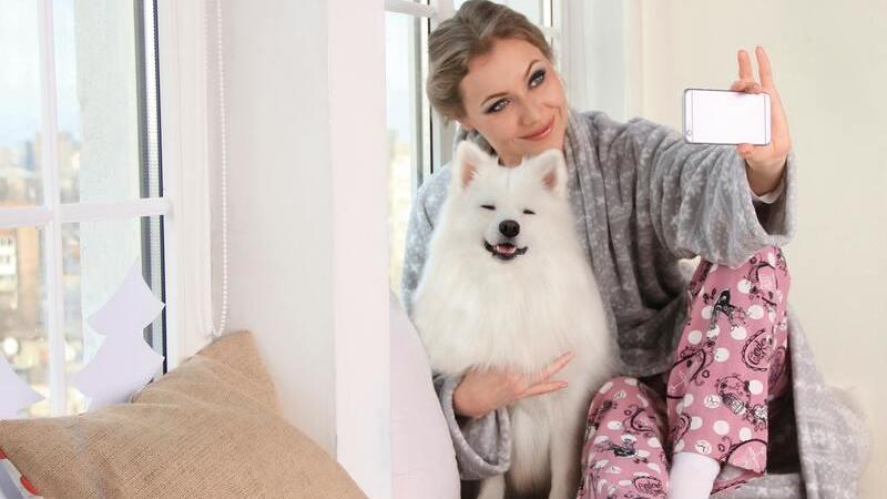 Mulher de pijama tirando selfie com cachorro
