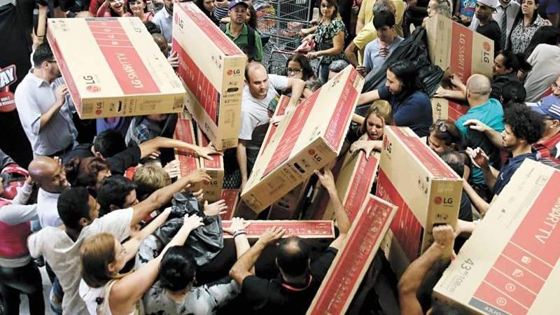 Multidão segurando televisores em caixas na Black Friday no Brasil