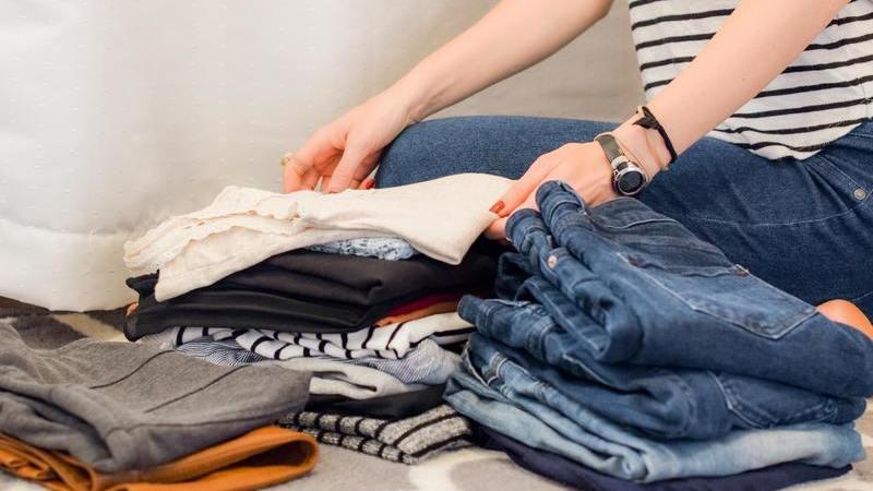 Pessoa dobrando roupas e as separando.