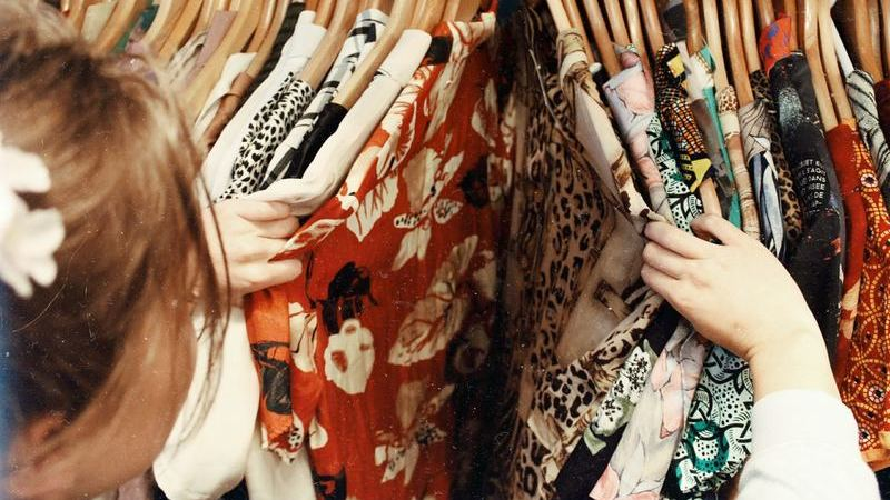 Roupas penduradas em loja com pessoa olhando pra elas