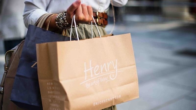 Pessoa segurando sacola de loja.