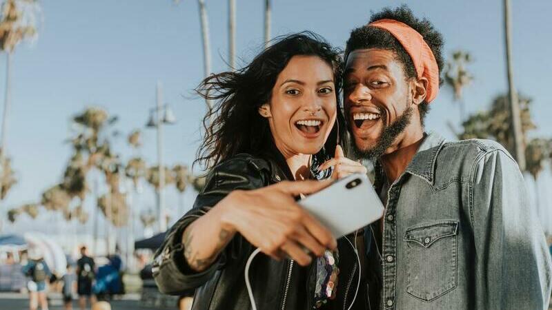 Homem e mulher tirando uma sefie em ponto turístico