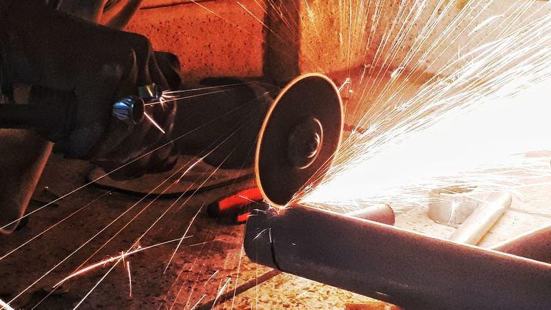 Serra circular cortando cano metálico com muitas faíscas