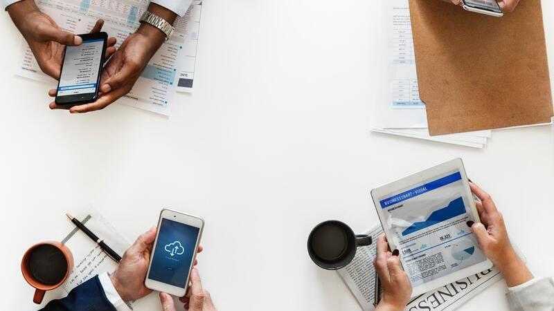 Três pessoas em uma mesa com papéis segurando tablets e smartphones