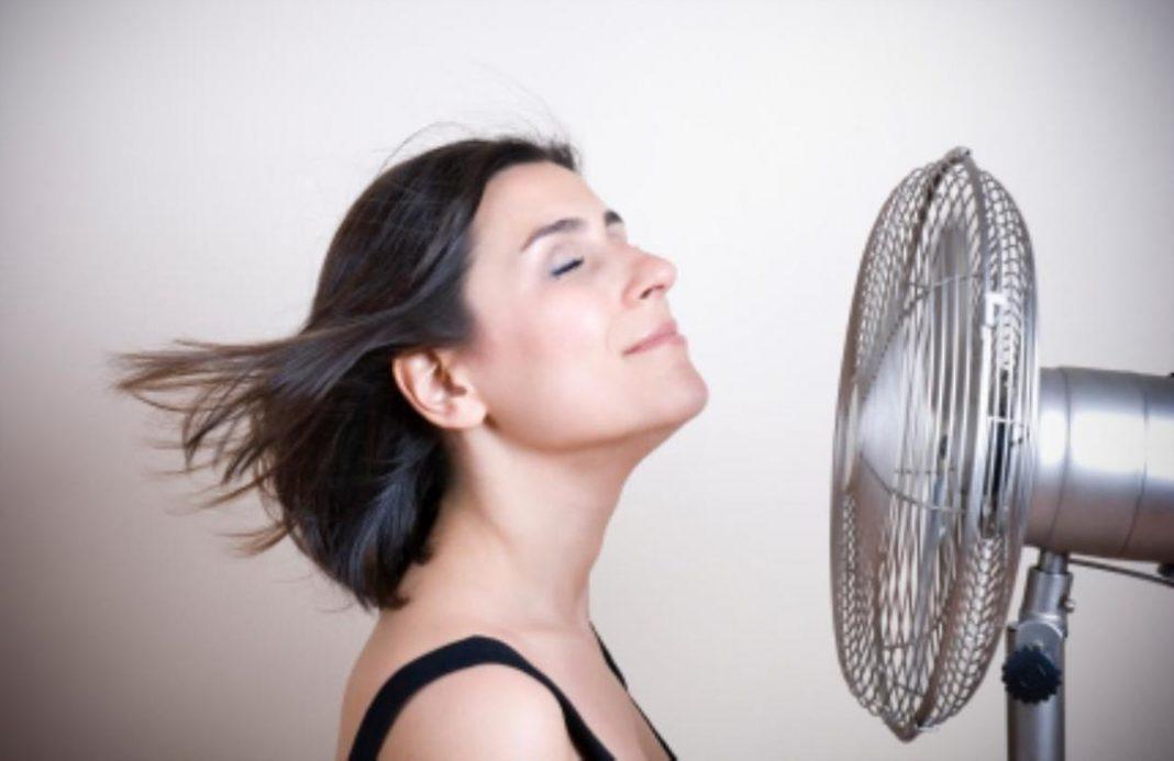 Mulher em frente a um ventilador com os cabelos voando