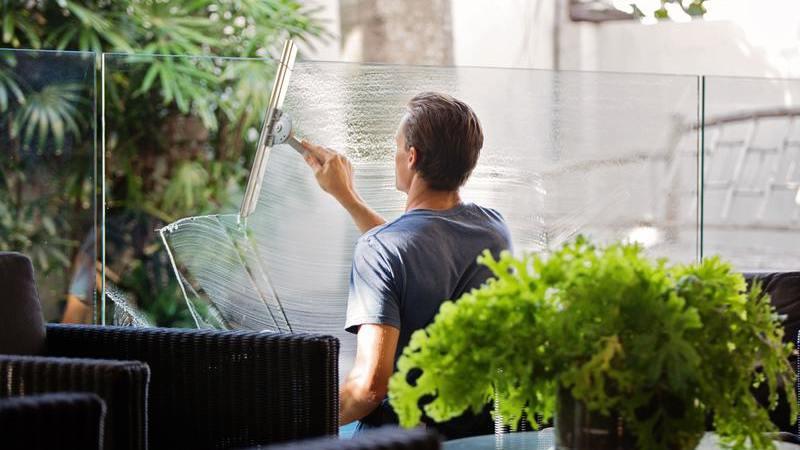 Homem limpando superfície de vidro com rodinho