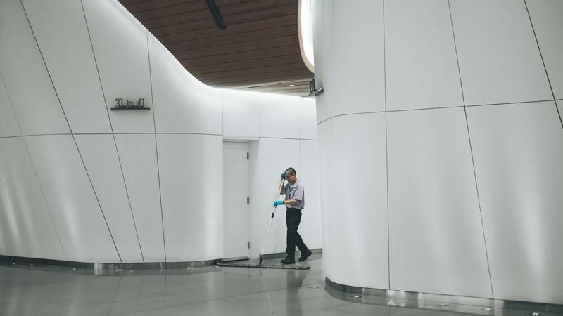 Zelador passando um rodo em saguão de prédio
