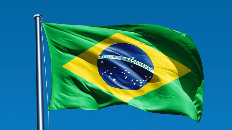 Bandeira do Brasil em mastro sob céu azul