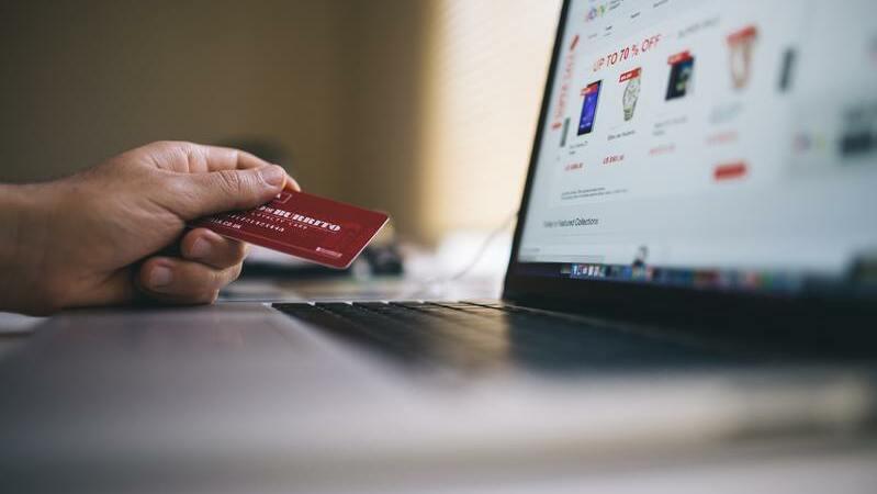 Pessoa segurando cartão de crédito e usando computador para comprar no atacado online.