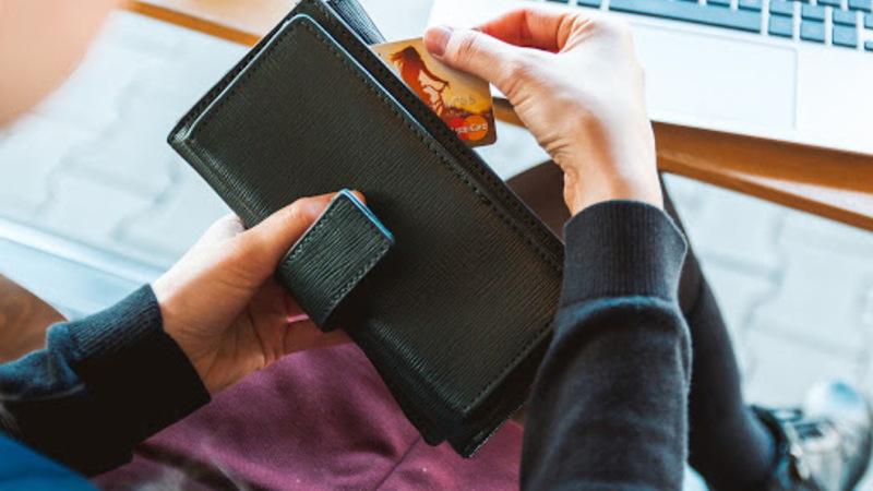 pessoa retirando cartão de crédito da carteira