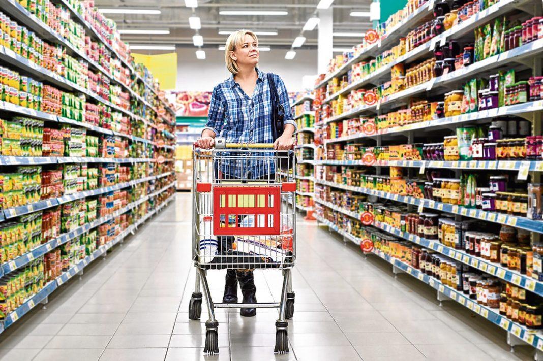 Mulher com carrinho de compras em corredor de supermercado