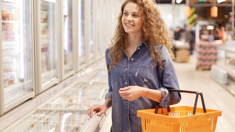 Mulher com cesta de compras no supermercado