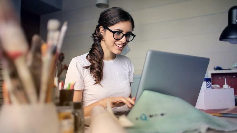 Mulher de óculos mexendo em um notebook no escritório