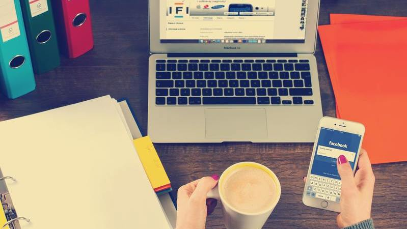 Mulher segurando smartphone e caneca sentada de frente para mesa com notebook aberto