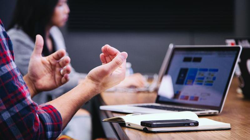 Close em mãos de pessoa falando em reunião. Há uma mesa com um notebook, um caderno e um smartphone