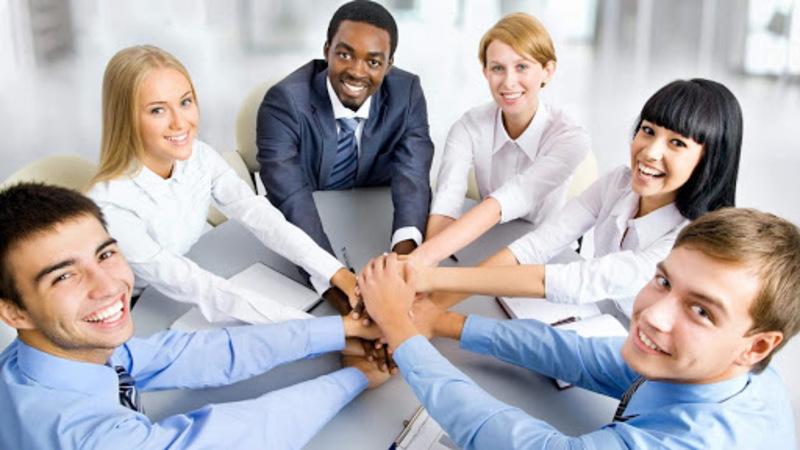 grupo de pessoas de mãos dadas sob a mesa