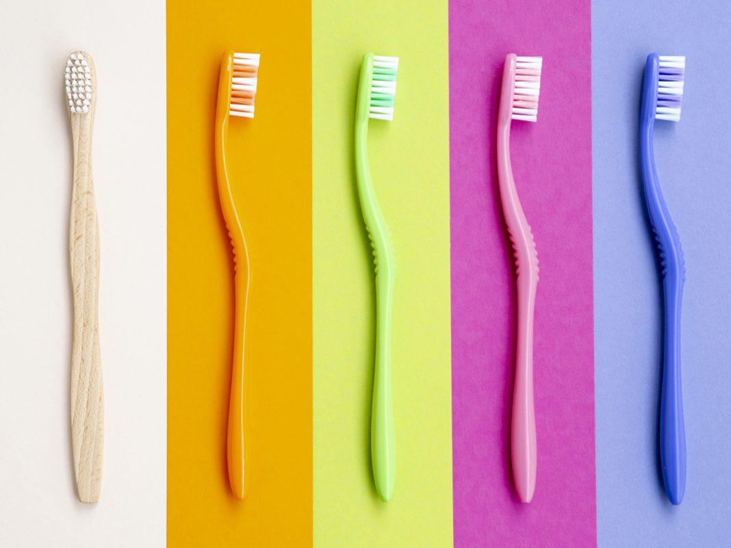 Escovas de dentes coloridas enfileiradas, com uma diferente, em cor natural