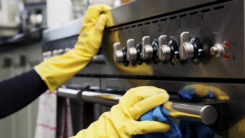 Pessoa de luvas de borracha limpando fogão