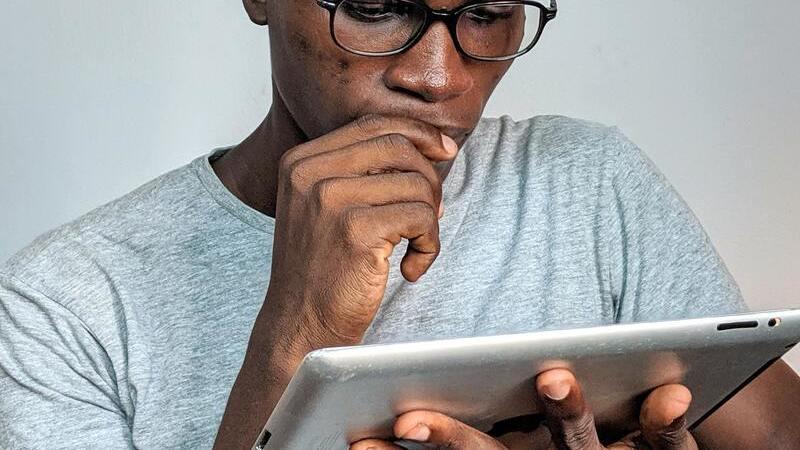 Homem de óculos segurando tablet com expressão de dúvida