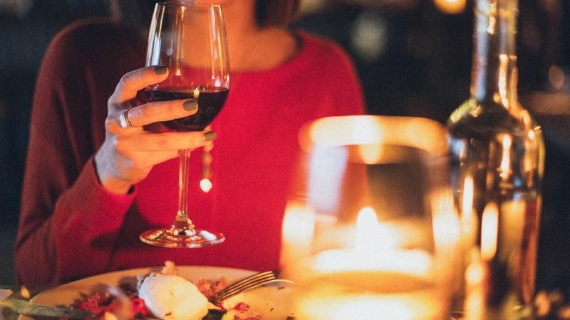 Mulher em jantar bebendo uma taça de vinho