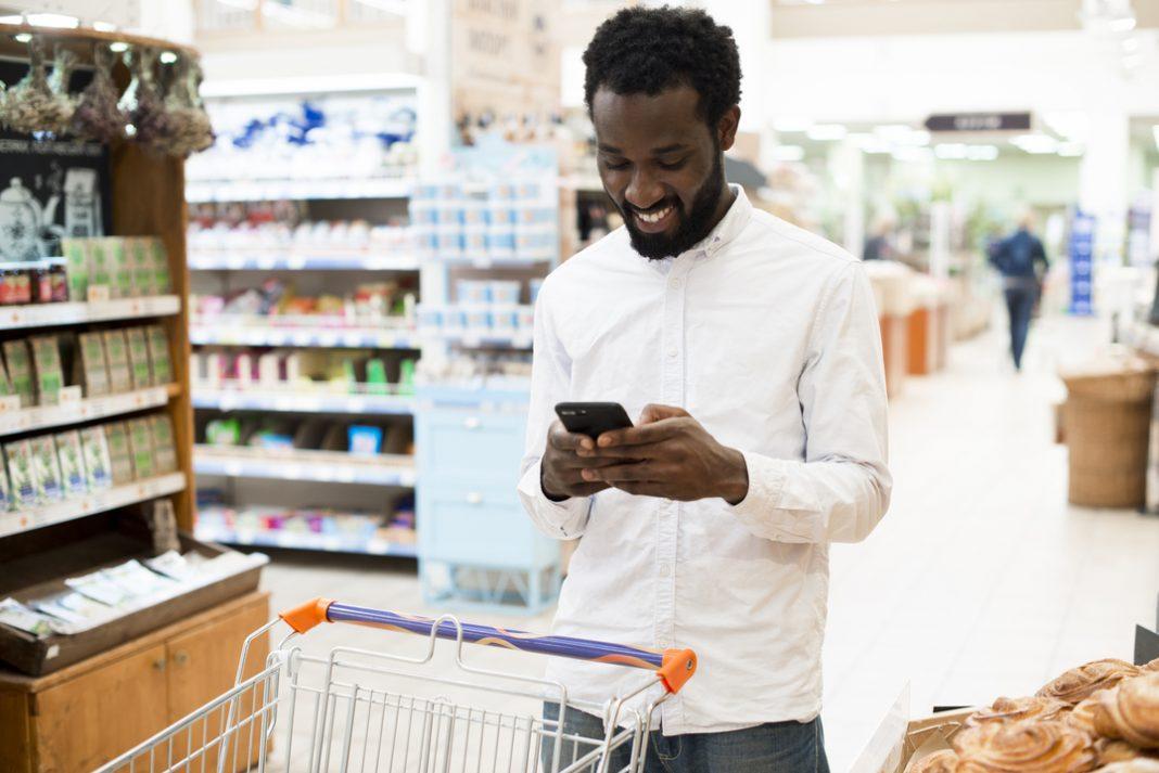 Homem em mercearia olhando para o celular e sorrindo