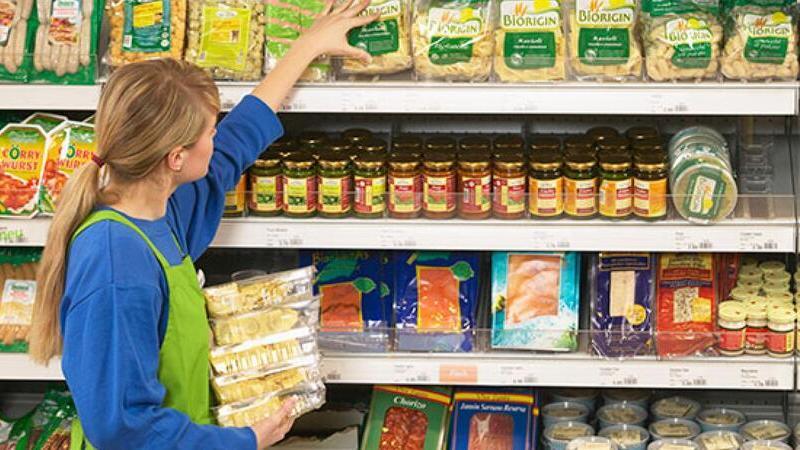 Pessoa organizando produtos na gôndola de supermercado