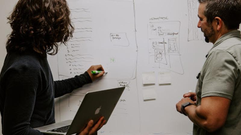 Duas pessoas diante de um quadro de ideias