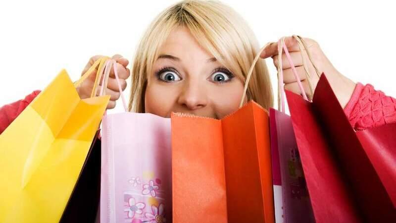 Mulher de olhos arregalados segurando várias sacolas de compras