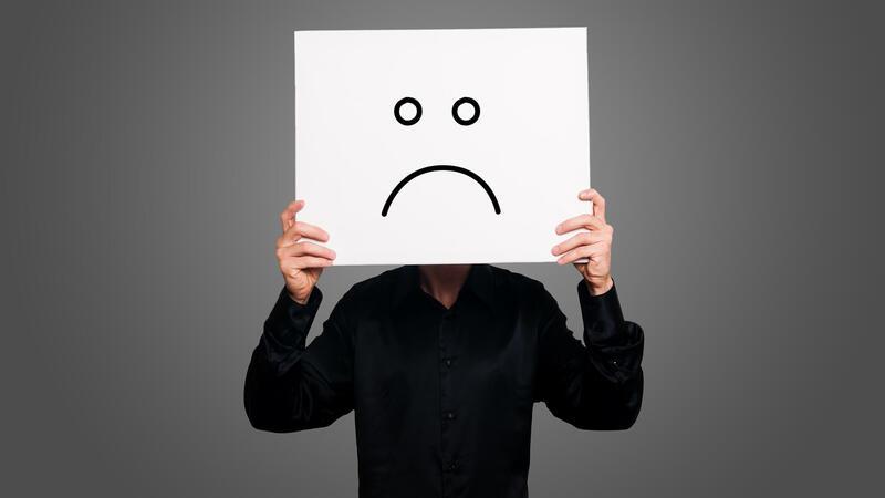 Homem com cartaz com desenho de rosto triste
