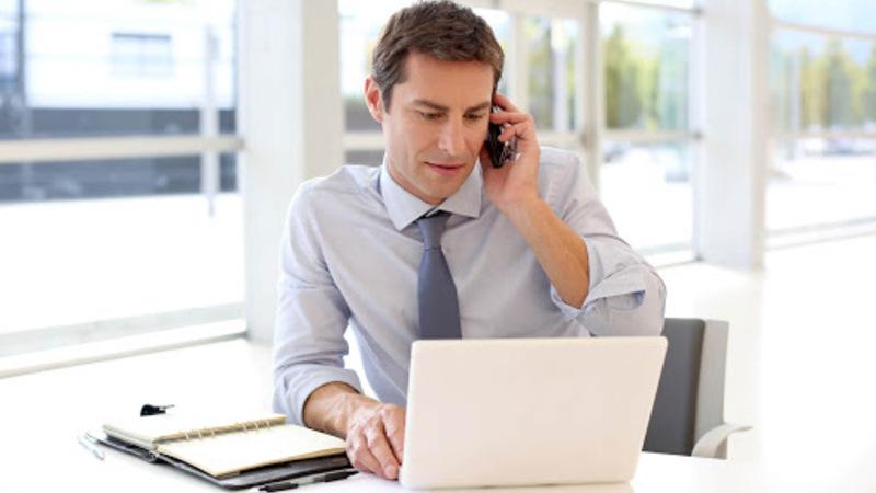 homem em seu escritório falando ao telefone
