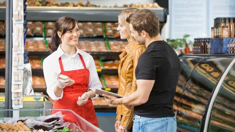 Vendedora de avental vermelho mostrando produto para um homem e uma mulher