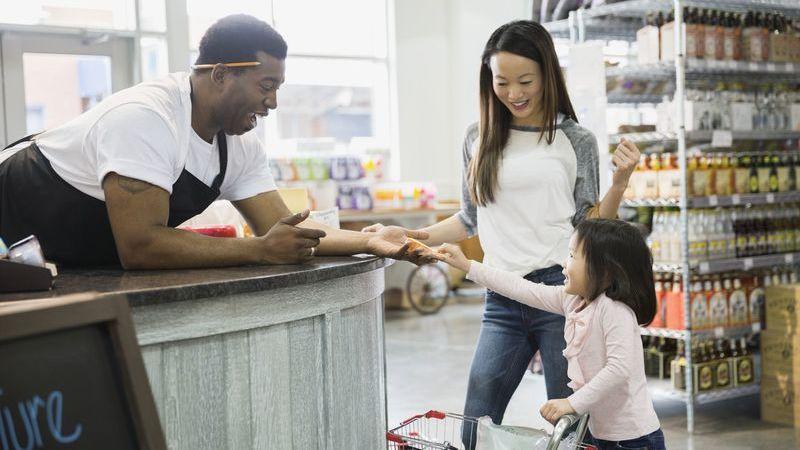 Atendente de loja brincando com filha de cliente.