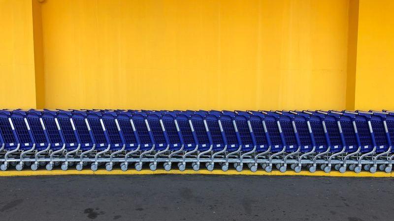 Vários carrinhos de compras azuis enfileirados próximos a parede amarela.