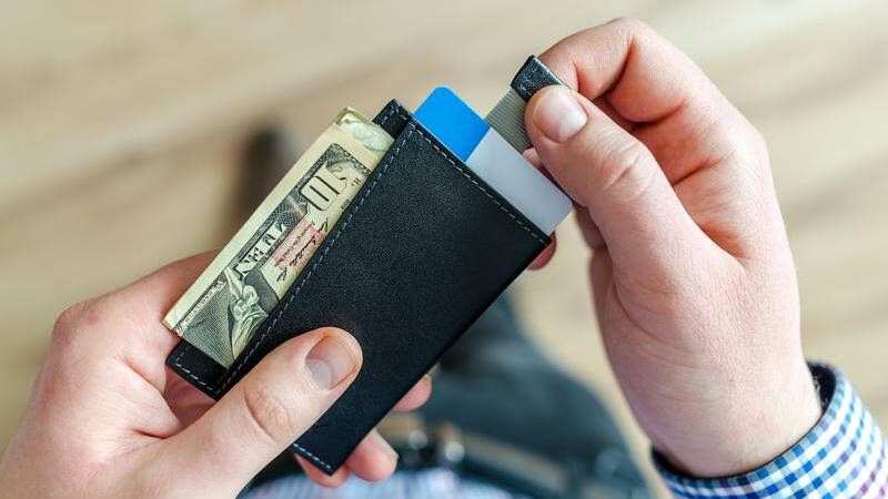 Pessoa segurando carteira com dinheiro e cartões de crédito