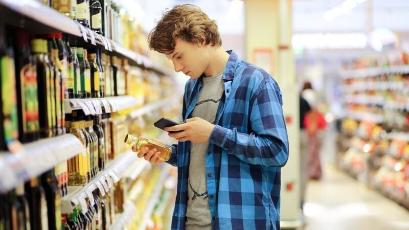 Garoto no supermercado segurando vidro de azeite e smartphone