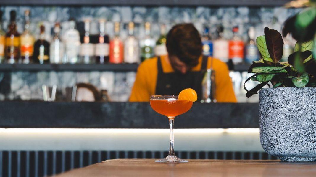 Drink laranja à frente com bar desfocado ao fundo.