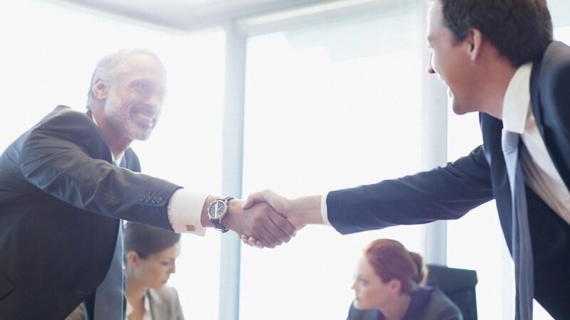 Dois homens apertando as mãos em reunião de negócios