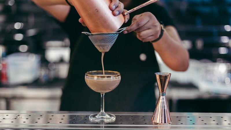 Bartender fazendo um drink com licor amarronzado