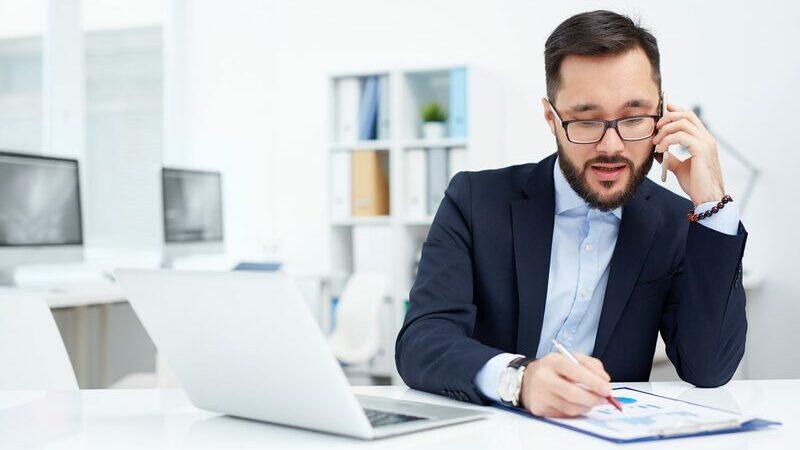 Homem de barba usando o telefone e lendo um catálogo