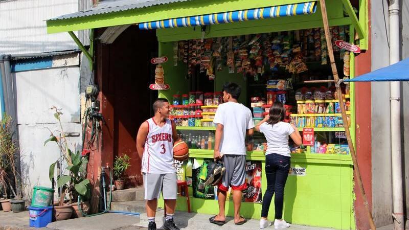 Fachada de loja pequena com três pessoas