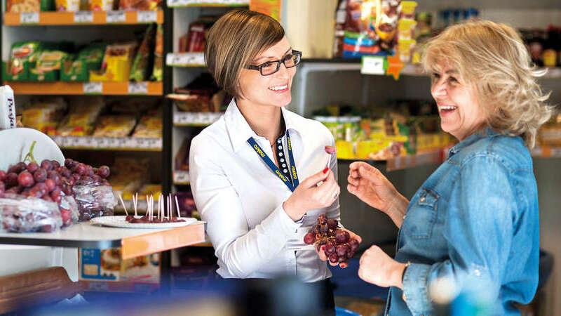 Mulher oferecendo uvas em degustação de supermercado para cliente