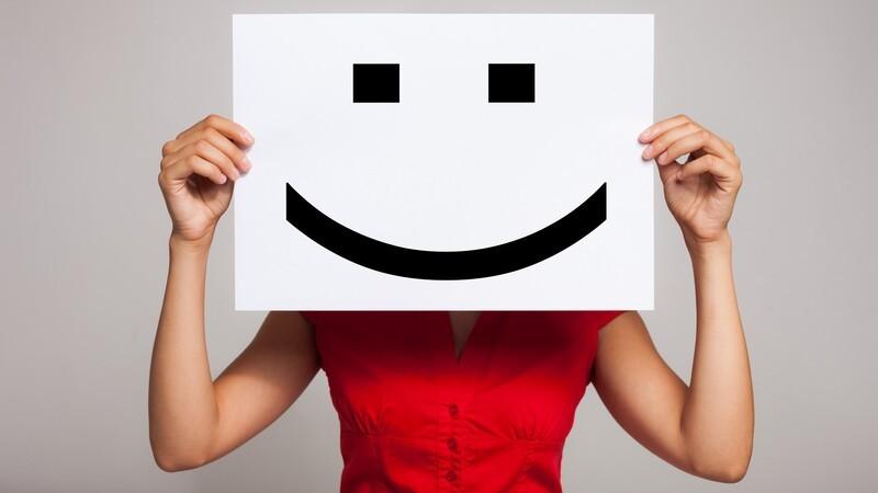 Mulher segurando um cartaz com carinha feliz na frente do rosto