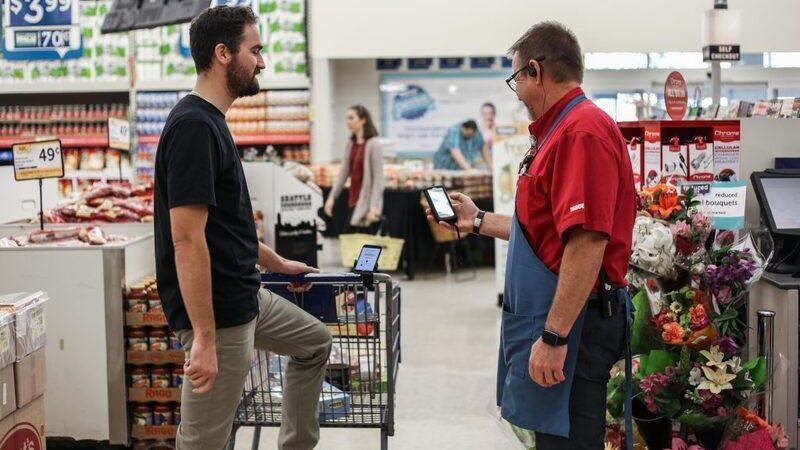 Homem com carrinho de compras sendo atendido por homem de avental vermelho no supermercado