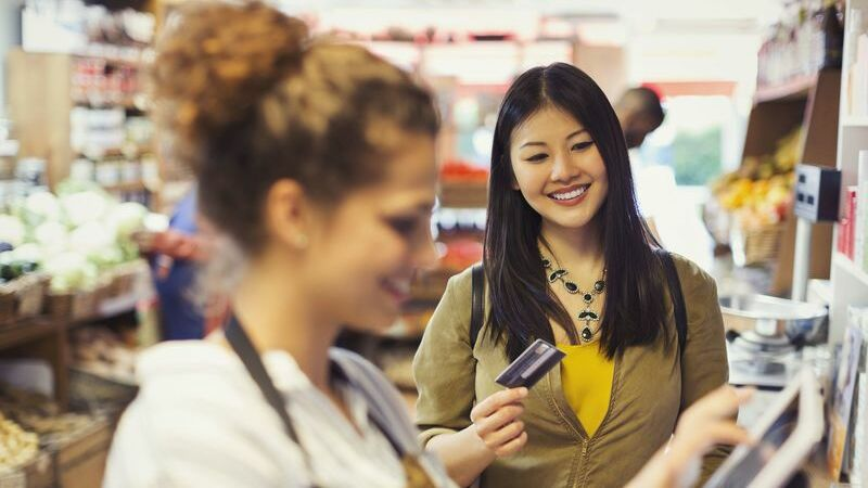 Mulher segurando cartão de crédito no caixa da loja
