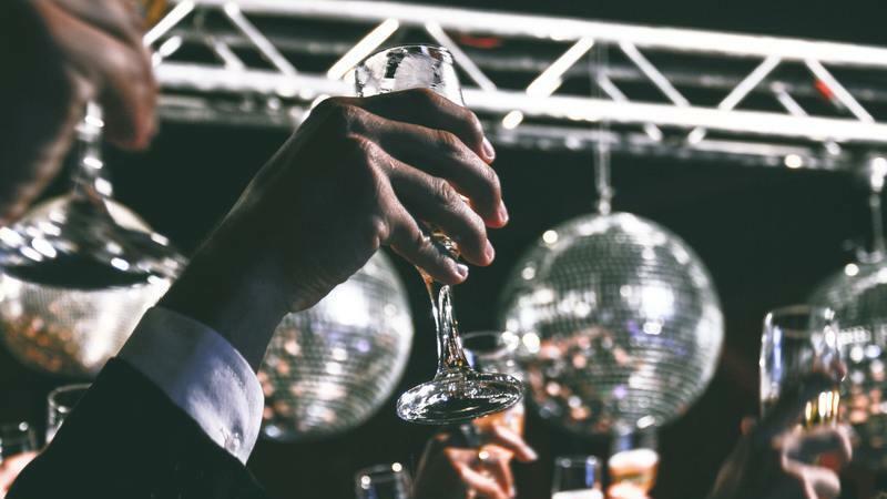 pessoas festejando com taças de champagne para o alto