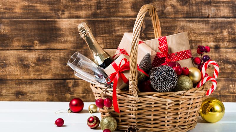 Cesta de Natal para funcionários com presentes, frutas, espumante, taças e decorações.