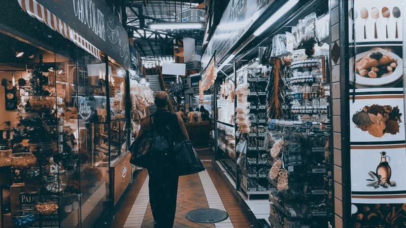 Pessoa andando num corredor entre várias lojas